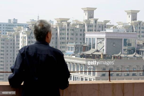 A man looks at antique buildings built on a rooftop of a tall building at Pingyang road on August 7 2014 in Taiyuan Shanxi province of China