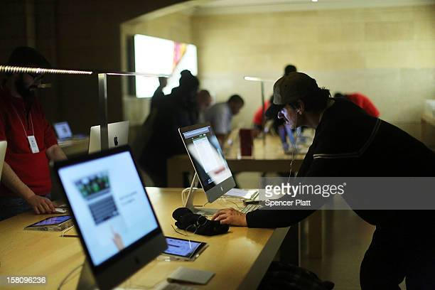 A man looks at Apple products at the Apple retail store in Grand Central Terminal on December 10 2012 in New York City Apple Inc stock was down $456...