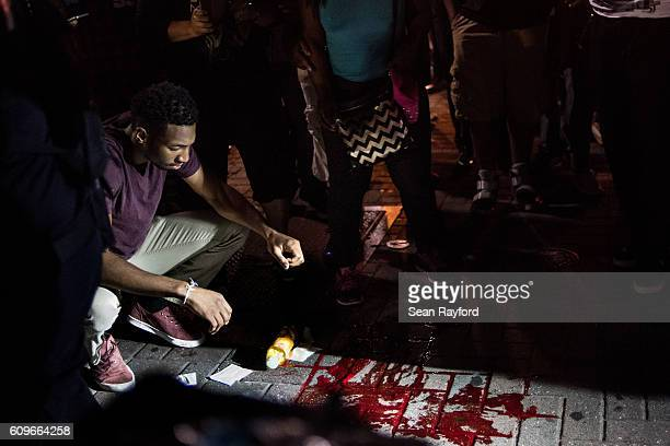 Man looks at blood on the sidewalk in front of the Omni Hotel September 21, 2016 in Charlotte, NC. Protests in Charlotte began on Tuesday in response...