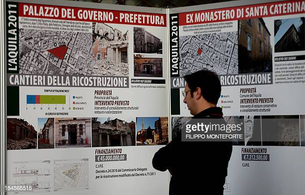 A man looks at boards reading 'works for the Palazzo del governo ' on October 22 2012 in L'Aquila Six Italian scientists and a government official...