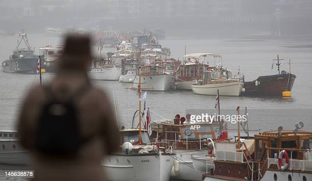 A man looks at boats that will be part of the Jubilee river pageant are docked in thick fog in Putney on the river Thames for the Jubilee...