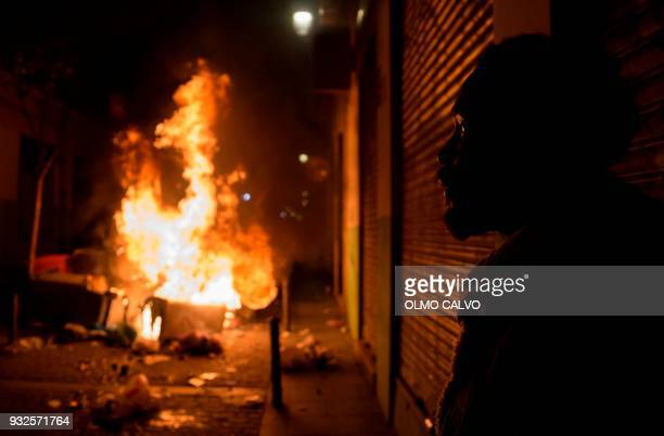 A man looks at burning trash cans during a protest following the death of a street vendor at Lavapies district in Madrid on March 15 2018 Migrants...