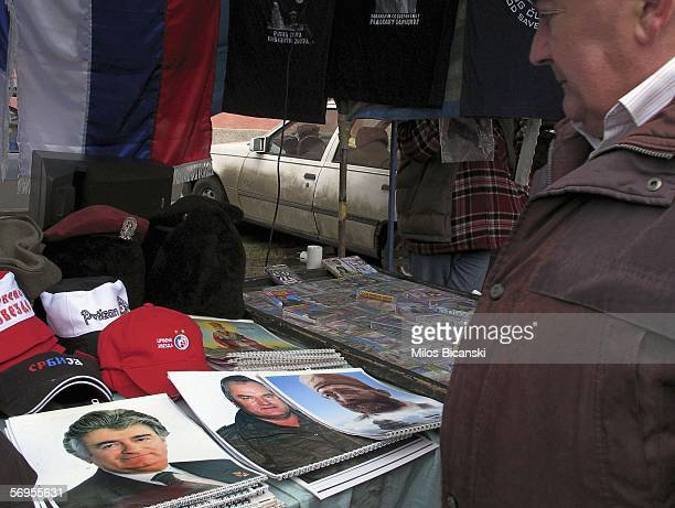 A man looks at calendars with pictures of top war fugitives Bosnian Serb leader Radovan Karadzic and military commander General Ratko Mladic on...