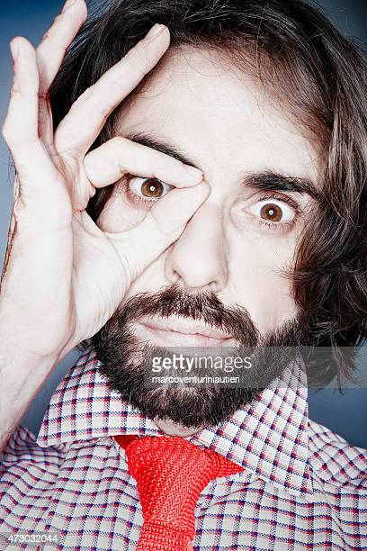 Man looks at camera while circling his eye with hand