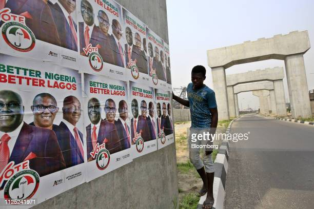 A man looks at campaign posters of Atiku Abubakar candidate of the main opposition People's Democratic Party near mono rail line pillers under...
