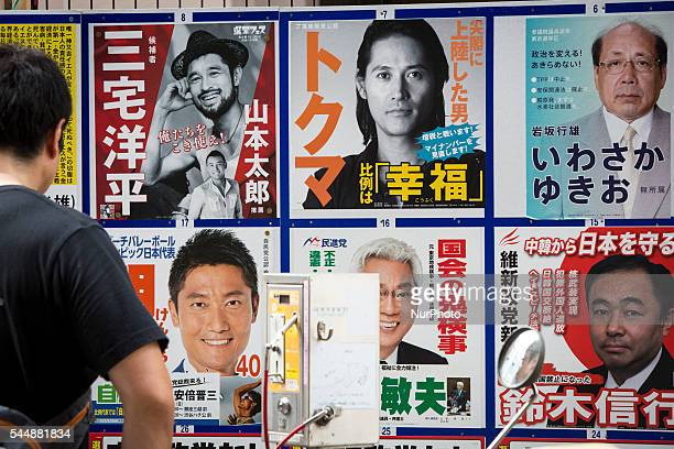 Man looks at candidates' posters with pictures for the 2016 Upper House election in Tokyo, Japan, on Monday, July 4, 2016. Japanese voters will fill...