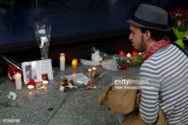 A man looks at candles letters and flowers placed for the victims of Madrid train bombings outside a memorial monument at Atocha railway station...
