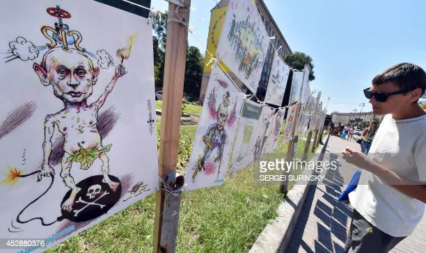 A man looks at caricatures of Russian President Vladimir Putin at an openair exhibition by Ukrainian cartoonist architect and journalist Oleh Smal in...