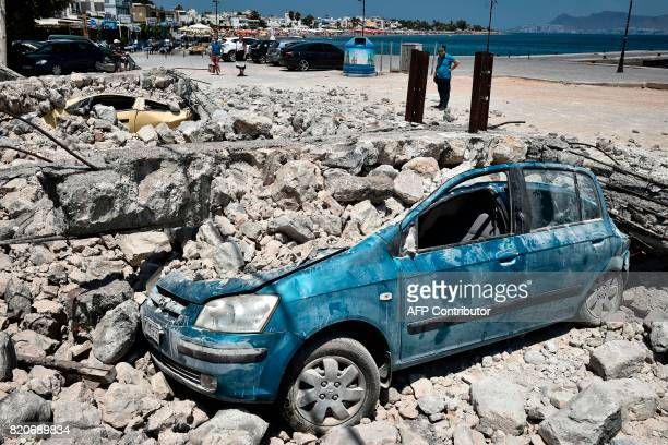 A man looks at cars under rubble on the Kos island on July 22 following an earthquake which struck the region Two foreigners died and more than 100...