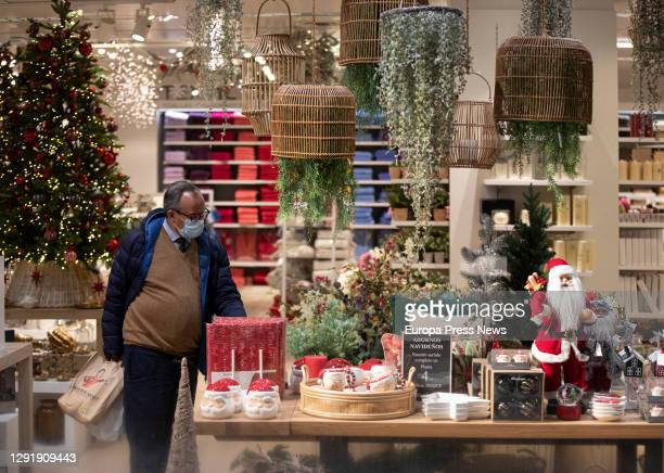 Man looks at Christmas-themed items in a shopping mall on December 17, 2020 in Sevilla .