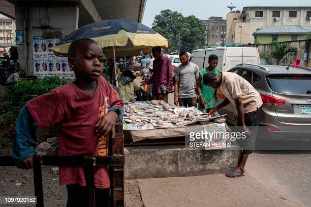 TOPSHOT A man looks at daily newspapers displayed under a bridge in Lagos on February 11 2019 Nigerians will participate in the national elections on...
