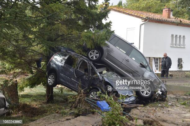 Man looks at damaged cars on October 16, 2018 in Conques-sur-Orbiel, near Carcassonne, southern France, following heavy rains that saw rivers...
