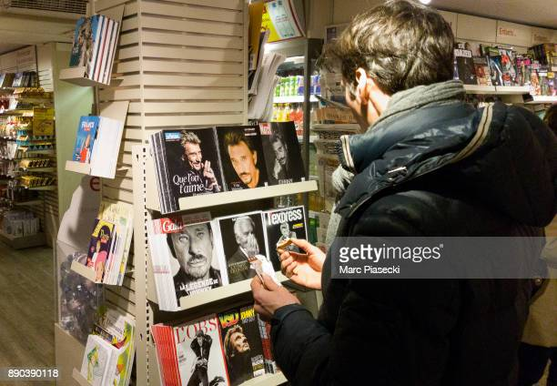 A man looks at different front pages of French magazines after singer Johnny Hallyday's death on December 11 2017 in Paris France Johnny Hallyday...