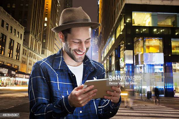 man looks at digital tablet at night in city.