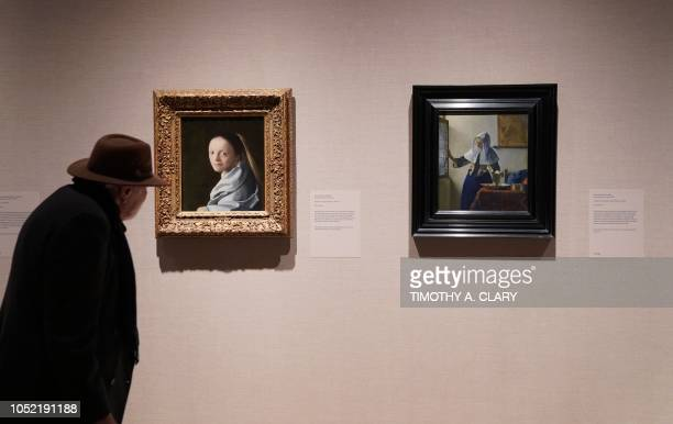A man looks at Dutch artist Johannes Vermeer's 'Study of a Young Woman' and 'Young Woman with a Water Pitcher' during a press preview at The...