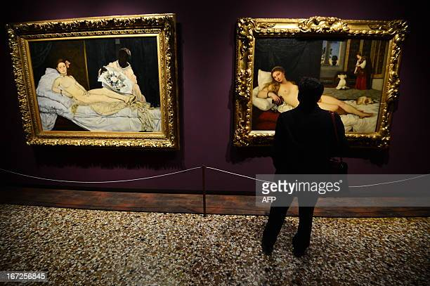A man looks at Edouard Manet's 'Olympia' and Titian's 'Venus of Urbino' on April 232013 in Venice as he visits the exhibition 'Manet Return to...