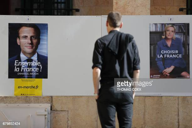 A man looks at election posters of independent centrist French presidential candidate Emmanuel Macron and farright Front National candidate Marine Le...