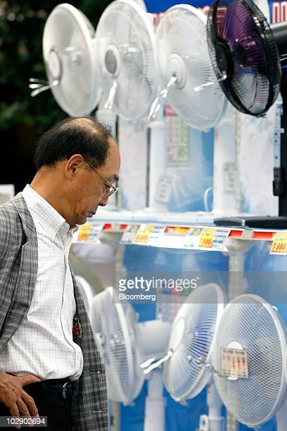 A man looks at electric fans displayed for sale at an electronics store in Tokyo Japan on Tuesday July 13 2010 Tokyo Electric Power Co Asia's biggest...