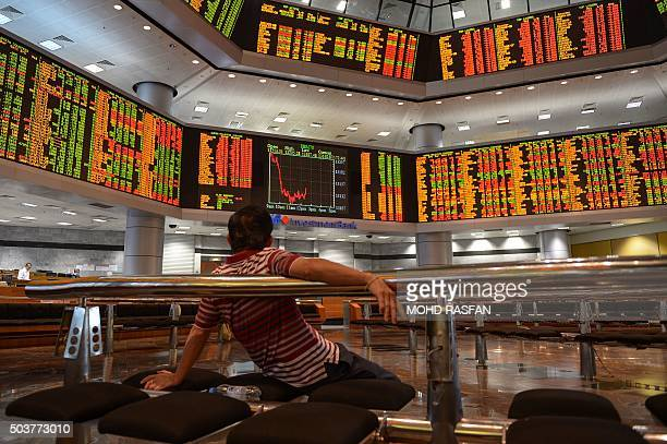 A man looks at electronic display boards as he monitors stock movements at a private trading firm in Kuala Lumpur on January 7 2016 Chinese markets...