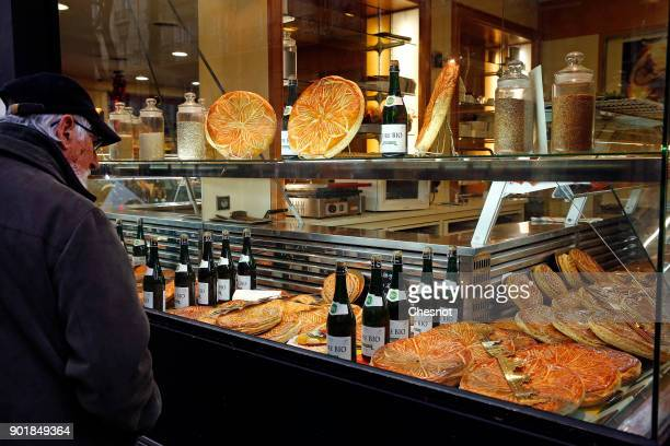 A man looks at Epiphany cakes or Twelfth Night cakes displayed in the window of a pastry shop on January 06 2017 in Paris France The 'galette des...