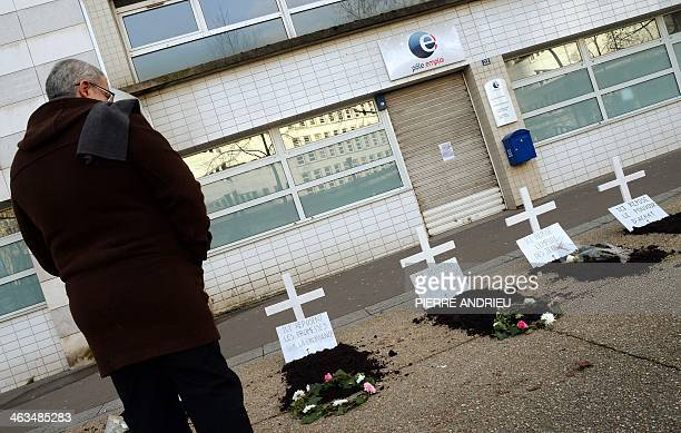 A man looks at fake graves with placards reading 'Here rests the promises of Hollande' created by demonstrators to symbolize and protest against what...