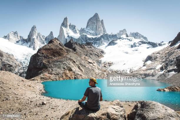 man looks at fitz roy mountain and turquoise lake in patagonia - chalten stock pictures, royalty-free photos & images