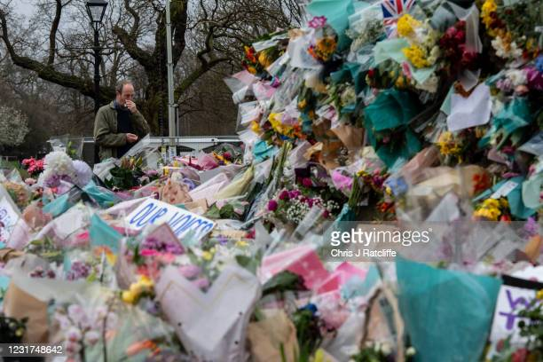 Man looks at floral tributes left at Clapham Common bandstand where people continue to pay their respects to Sarah Everard on March 16, 2021 in...