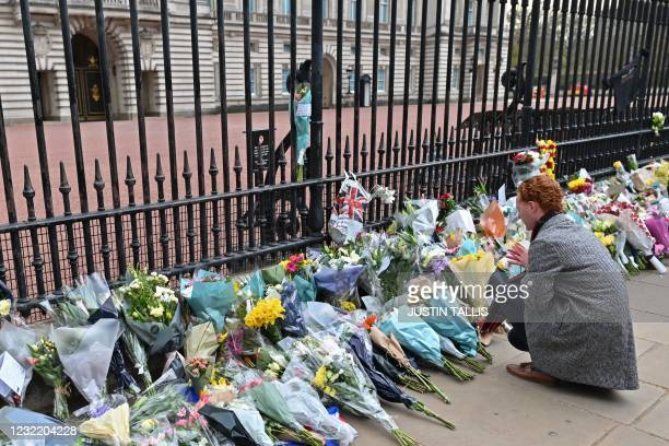 Man looks at floral tributes left at the gates of Buckingham Palace in central London on April 9, 2021 after the announcement of the death of...