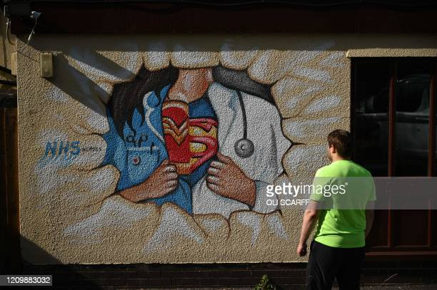 A man looks at graffiti depicting the badge of a superhero under a nurse's and doctor's uniform in homage to the efforts of NHS staff during the...