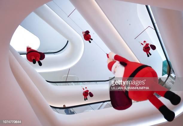 TOPSHOT A man looks at hanging Santa Claus Christmas display at a shopping mall in central Bangkok on December 25 2018