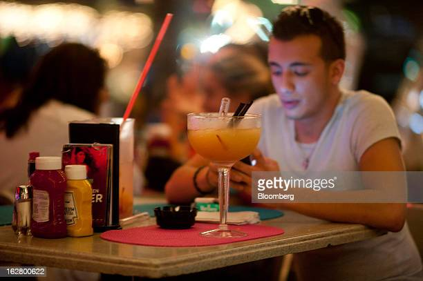 A man looks at his cell phone with a drink at a restaurant on Ocean Drive in the South Beach neighborhood of Miami Beach Florida US on Tuesday Feb 19...