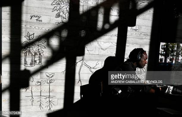 A man looks at his computer at a Starbucks coffee shop in Washington DC on October 18 2018