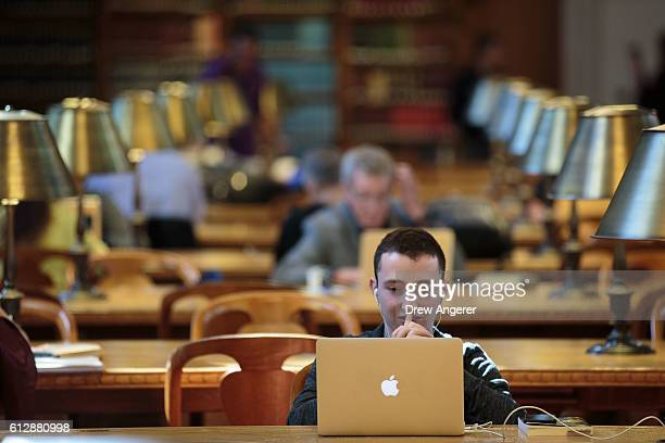 A man looks at his laptop inside the Rose Main Reading Room at the New York Public Library October 5 2016 in New York City The Rose Main Reading Room...