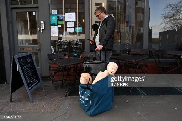 Man looks at his phone as he stands alongside a bag with shop dummies in Brighton, southern England on February 12, 2020. - The businessman from Hove...