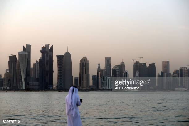TOPSHOT A man looks at his phone on the corniche in the Qatari capital Doha on July 2 2017 / AFP PHOTO / STR