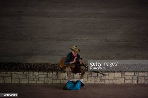 A man looks at his phone on the river walk on April 1 2020 in downtown San Antonio Texas during a stay at home order amid the novel coronavirus...