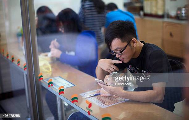 A man looks at his smartphone as he eats inside a 7Eleven convenience store in Taipei Taiwan on Monday Nov 9 2015 In his meeting Saturday with...