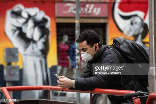 Man looks at his smartphone as he waits next to the entrance of an undergound station on March 11, 2020 in Milan, Italy. The Italian Government has...