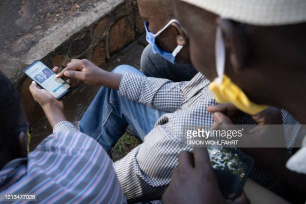 A man looks at his smartphone in Kigali Rwanda on May 18 showing the article on The New Times of the arrest of Felicien Kabuga one of the last key...