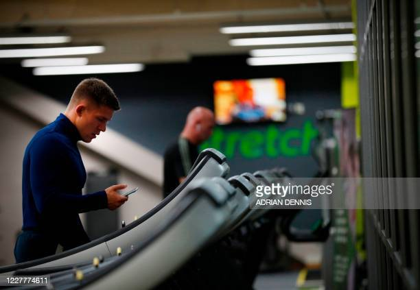 Man looks at his telephone during a warm down after exercising at Nuffield Health Sunbury Fitness and Wellbeing Gym in Sunbury-on-Thames, west of...