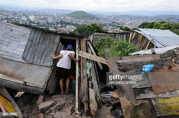 A man looks at his wrecked house on October 24 2008 at El Eden neighborhood on the side of El Picacho hill in Tegucigalpa Some 1000 inhabitants have...