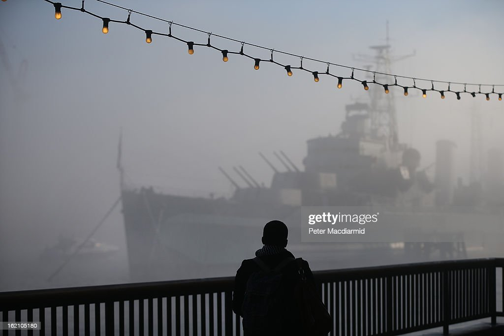A man looks at HMS Belfast as it emerges from early morning fog on The River Thames on February 19, 2013 in London, England. Heathrow was forced to cancel a number of flights and London City Airport suffered distruptions as a result of poor visibility due to fog.