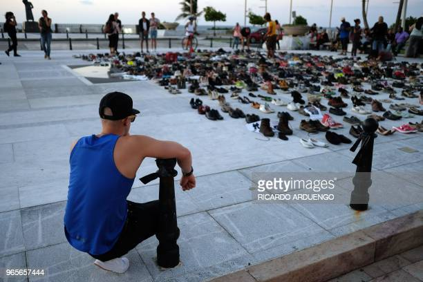 A man looks at hundreds of shoes displayed in memory of those killed by Hurricane Maria in front of the Puerto Rican Capitol in San Juan on June 1...