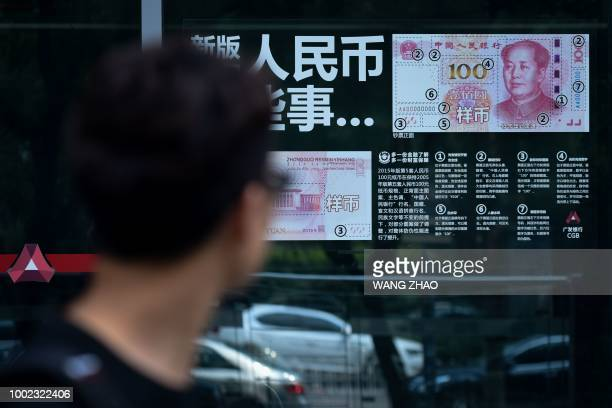 Man looks at information posted on a bank door showing how to distinguish real banknotes in Beijing on July 20, 2018. - China's yuan continued its...