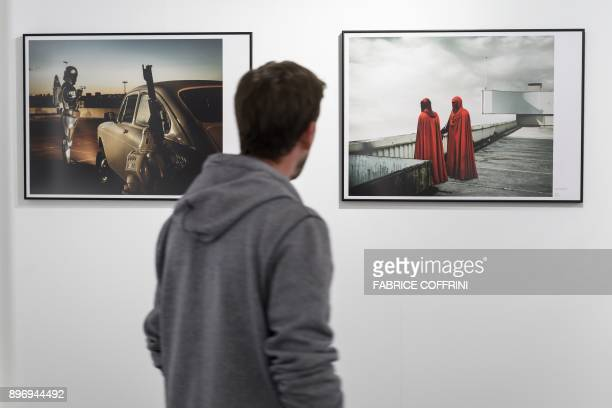 A man looks at 'Jango Fett' and 'Red Guards' digital photography by French artist Cedric Delsaux at science fiction museum The Maison d'Ailleurs...