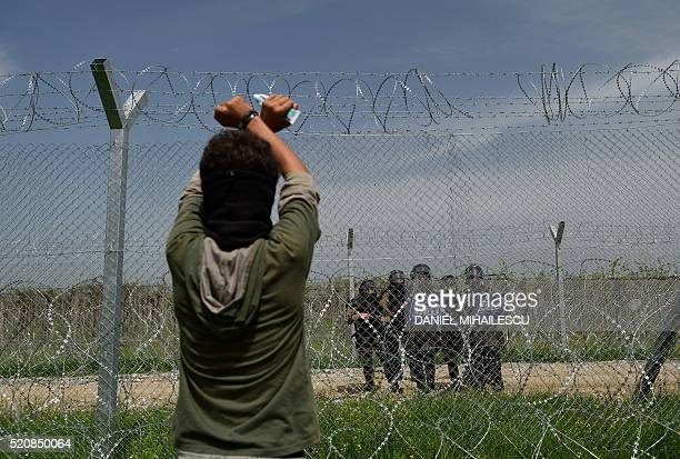 TOPSHOT A man looks at Macedonia police through a fence as migrants and refugees hold a protest to call for the reopening of the border near their...