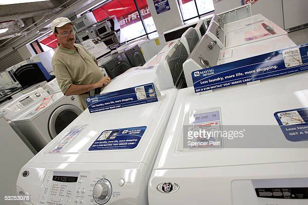 Man looks at Maytag and Whirlpool washers and dryers July 18, 2005 in New York City. Whirlpool on Sunday offered to buy Maytag, the maker of Hoover...
