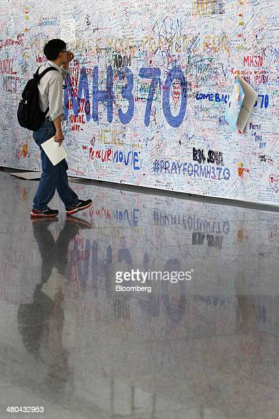 A man looks at messages written on a banner for the missing Malaysian Airline System Bhd Flight 370 at Kuala Lumpur International Airport in Sepang...