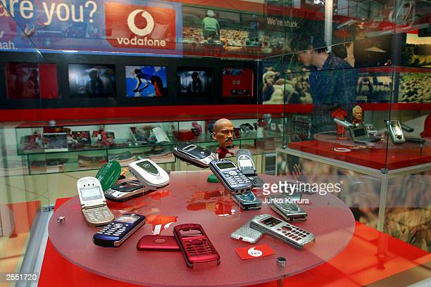 A man looks at mobile phones in the newly rebranded Vodafone KK store the new name of JPhone October 1 2003 in Tokyo Vodafone KK is Japan's third...