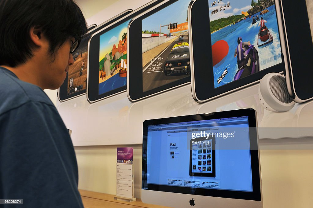 A man looks at monitors displaying the Apple iPad website at a computer store in Taipei on April 2, 2010. The touch-screen devices allow users to watch video, listen to music, play games, surf the Web or read electronic books. AFP PHOTO / Sam YEH